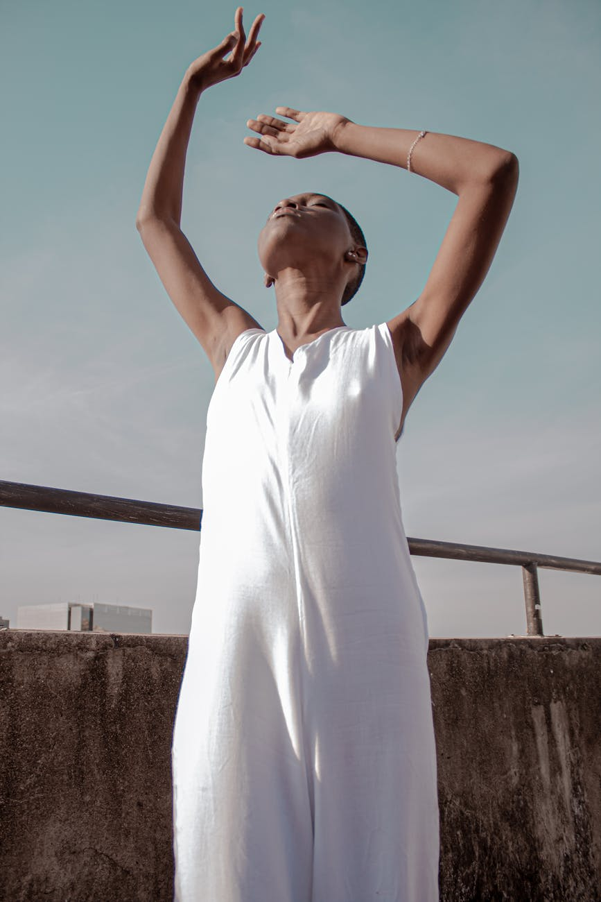 photo of woman in white dress posing with her head up and her hands raised